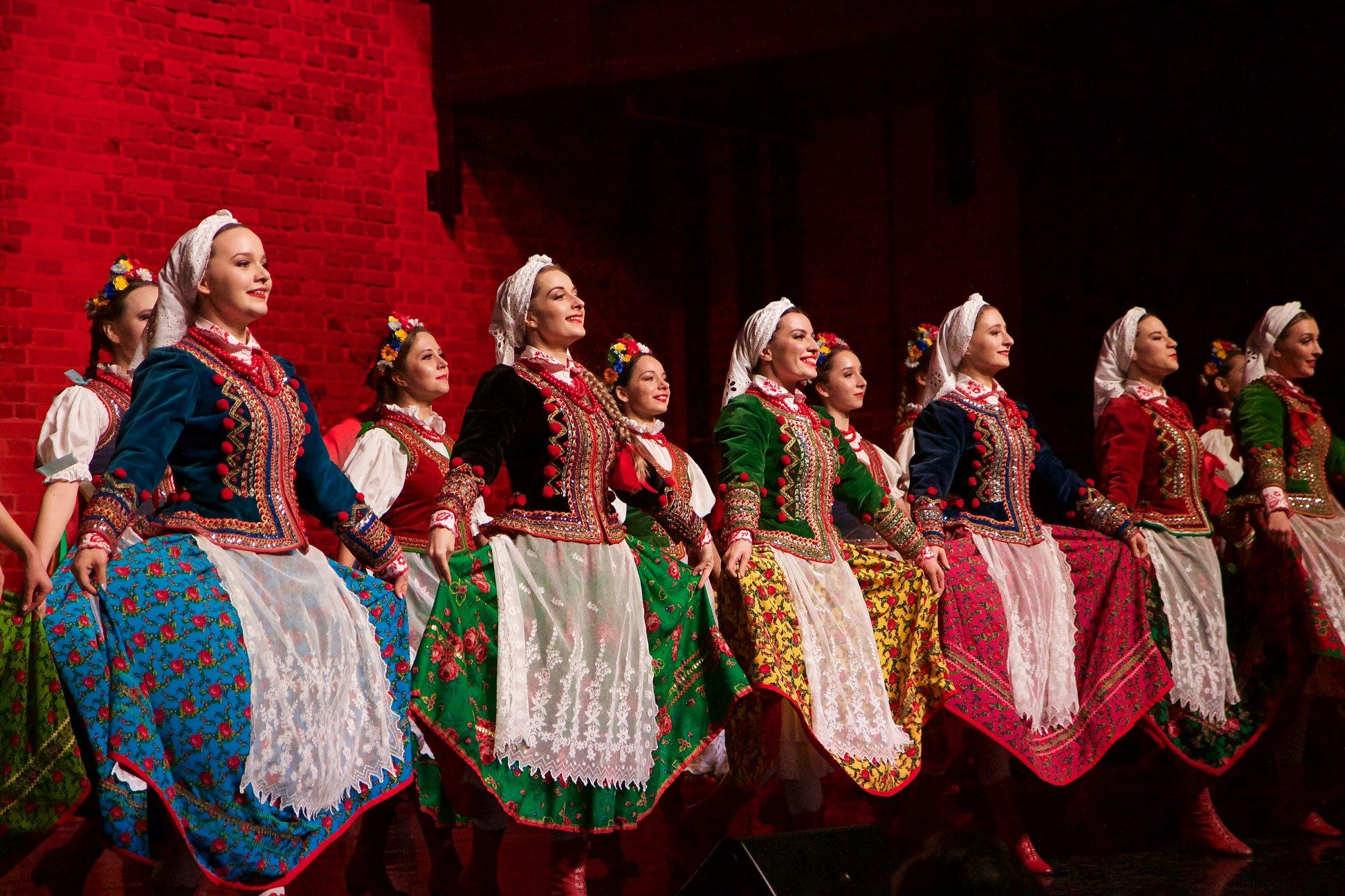 Grupa kobiet w wielokolorowych strojach ludowych. Trzymają rękami spódnice. Uśmiechają się.