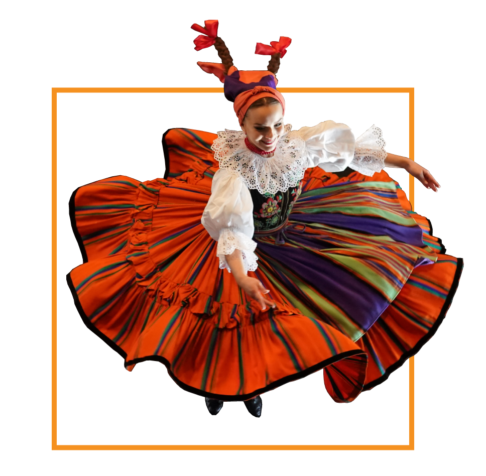 Kobieta w wielokolorowym stroju ludowym w trakcie wykonywania obrotu. Sukienka układa się na kształt koła. Ręce szeroko rozłożone. Dwa warkocze. Pomarańczowa, cienka ramka.