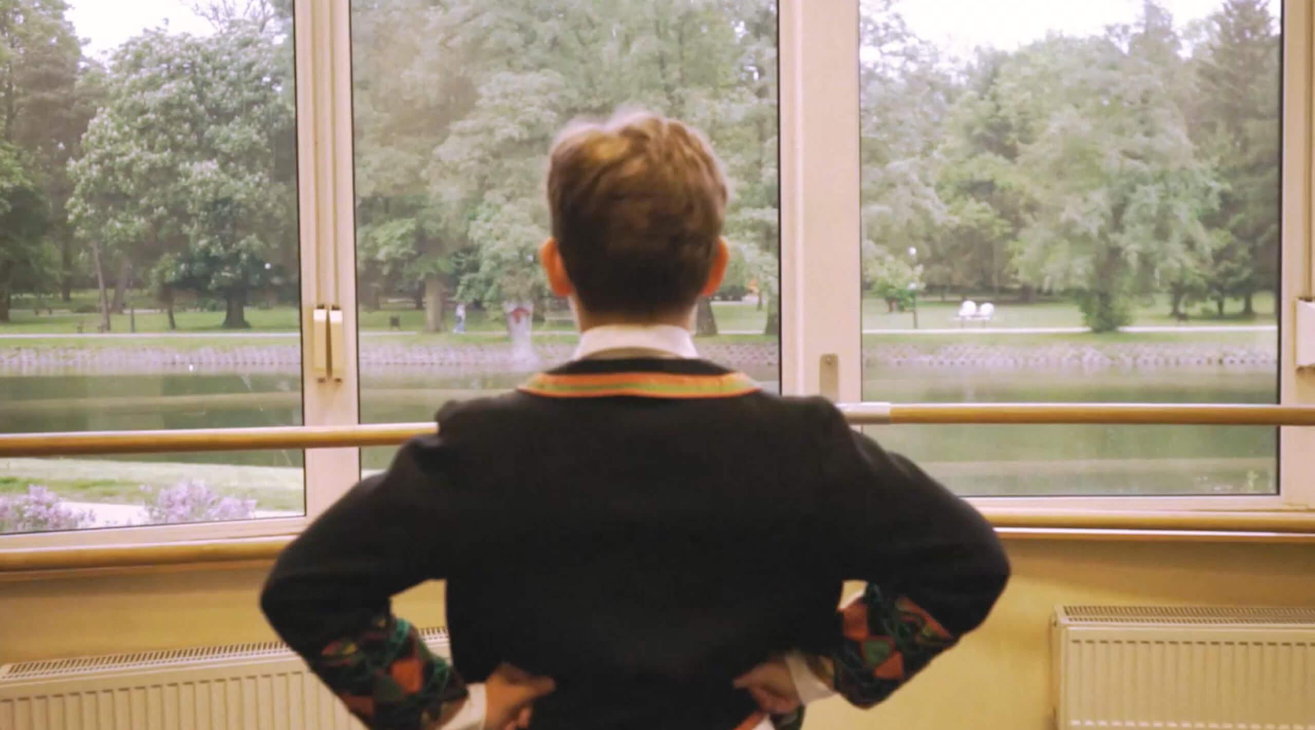 Chłopiec stojący tyłem. Patrzy w kierunku okna. Za oknem dużo drzew oraz zbiornik wodny.