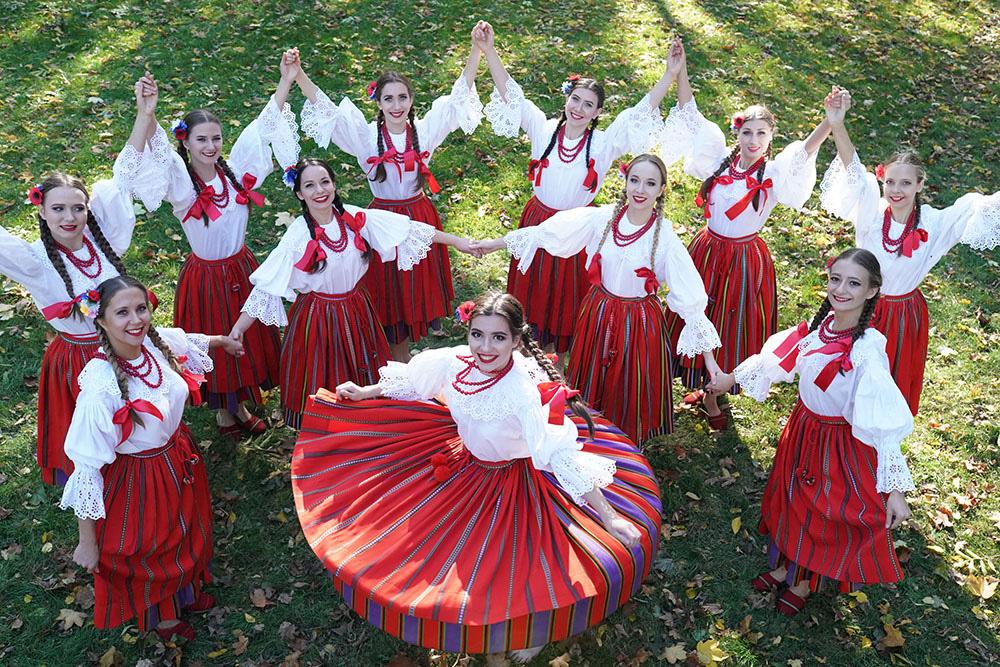 Grupa kobiet w białych ażurowych koszulach i czerwonych spódnicach ustawione w dwóch półkolach. W zewnętrznym półkolu kobiety trzymają się za ręce i unoszą je w górę. Wewnętrzne półkole - kobiety trzymają się za ręce. Po środku kobieta z szeroko rozłożonymi rękoma, w trakcie obrotu.