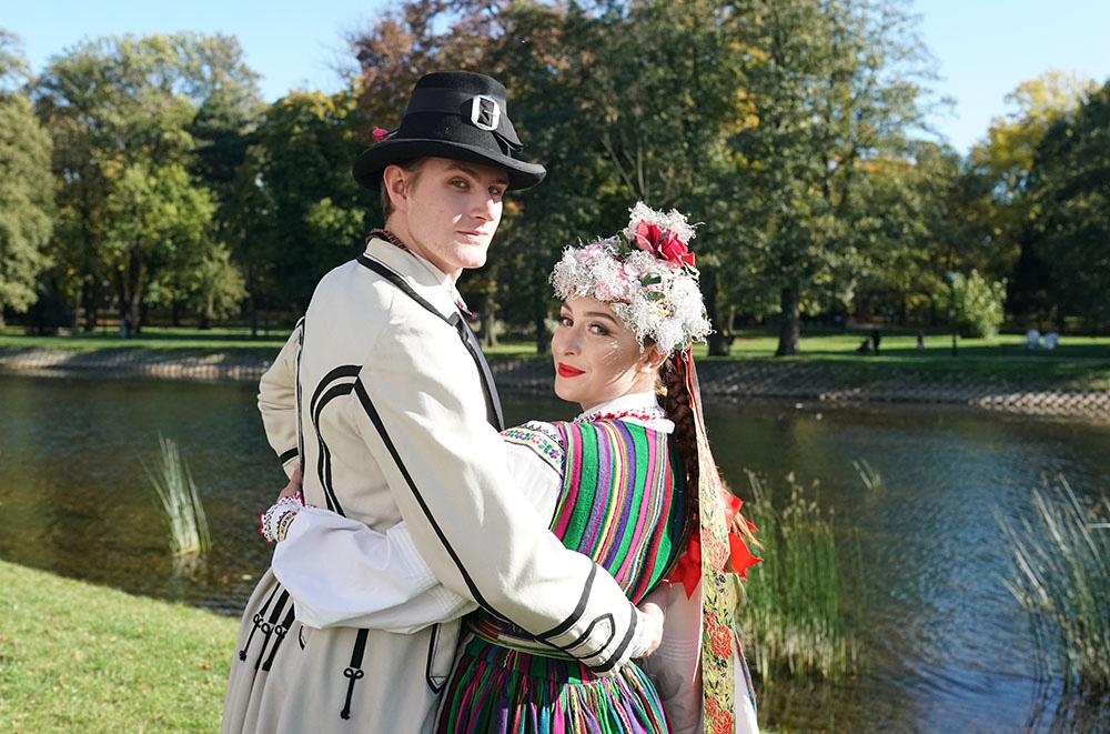 Para w wielokolorowych strojach ludowych. Kobieta ma na głowie czepiec, mężczyzna kapelusz. Obejmują się i patrzą w kierunku kamery.