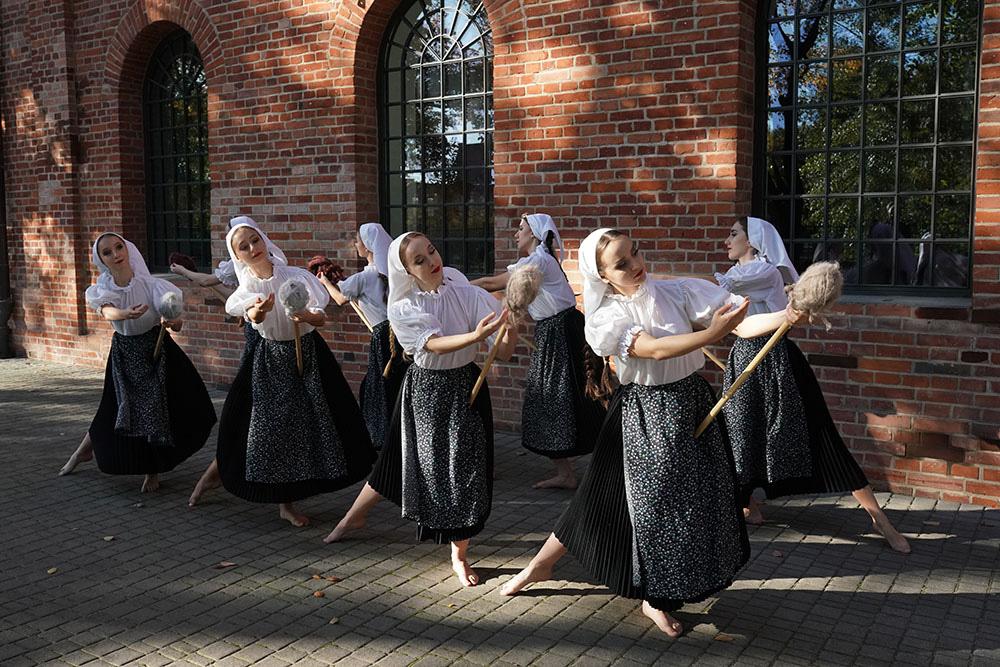 Osiem kobiet, tancerek. Cztery z przodu zwrócone w prawą stronę, cztery z tyłu zwrócone w lewą stronę. Mają na sobie białe koszulę, czarne plisowane spódnice, czarno-białe zapaski, białe chustki na głowie. W rękach trzymają podłużny przyrząd, na jego czubku włóczka.