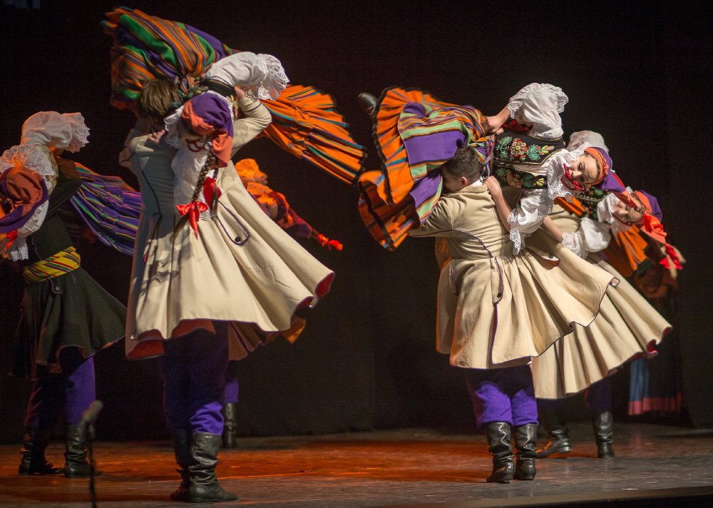Grupa ludzi tańczących w parach na scenie. Mają na sobie wielokolorowe stroje ludowe. Mężczyźni podnoszą kobiety przez ramię.
