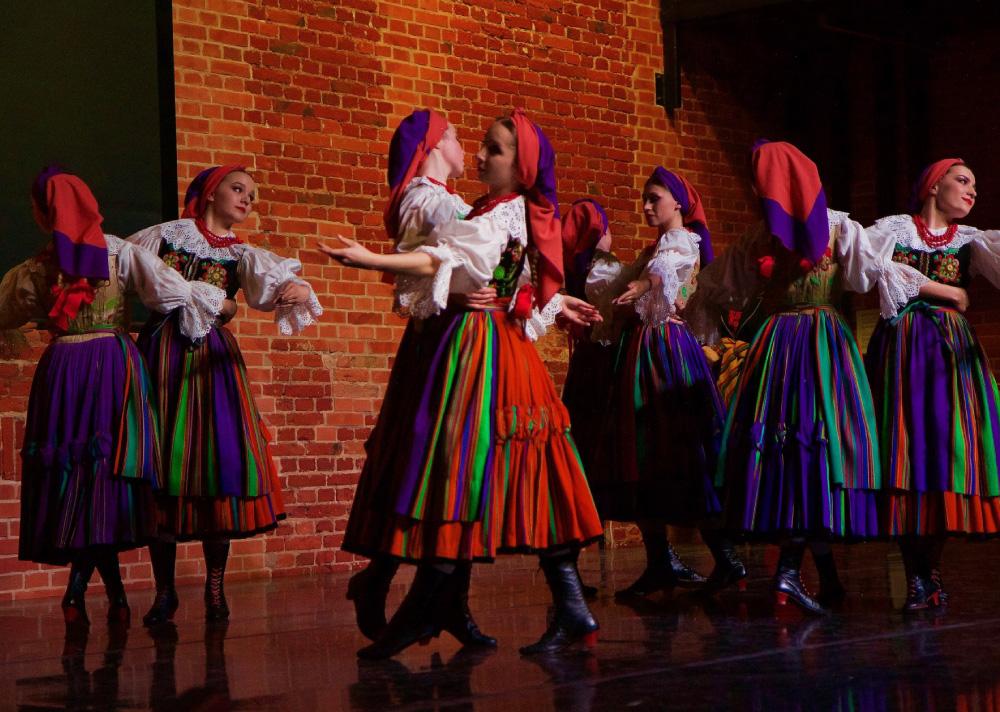 Grupa kobiet, tancerek na scenie. Mają na sobie wielokolorowe stroje ludowe. Na głowie pomarańczowo-fioletowe chustki. Ustawione w parach, trzymając się w pasie.