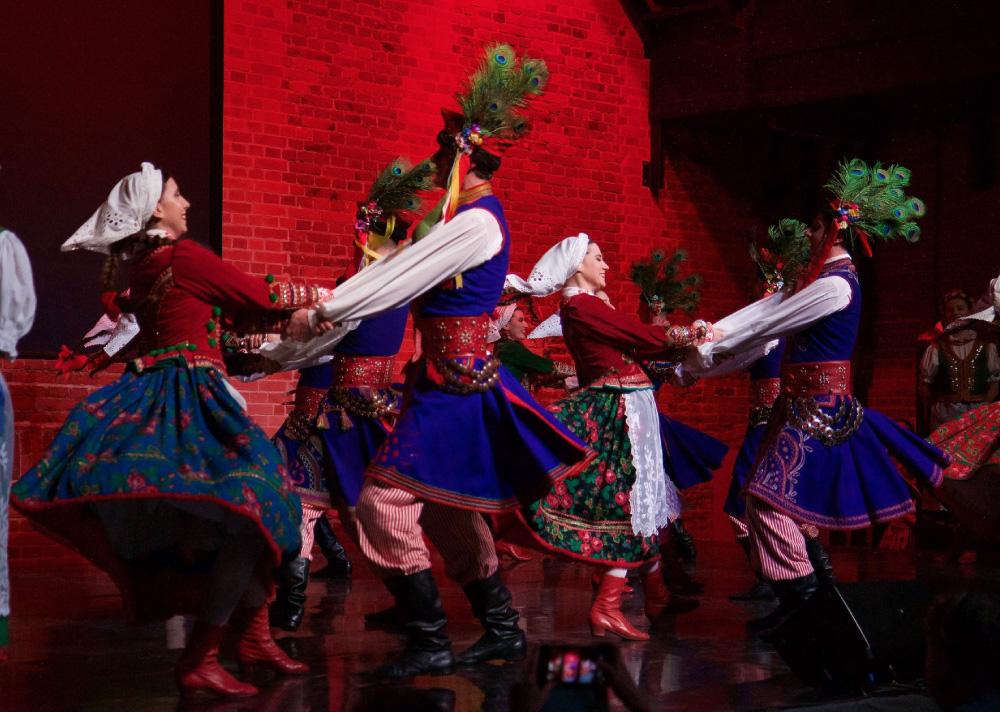 Grupa ludzi, tancerzy w krakowskich strojach ludowych. Tańczą w parach trzymając się za nadgarstki i odchylając się od siebie, na ugiętych nogach.