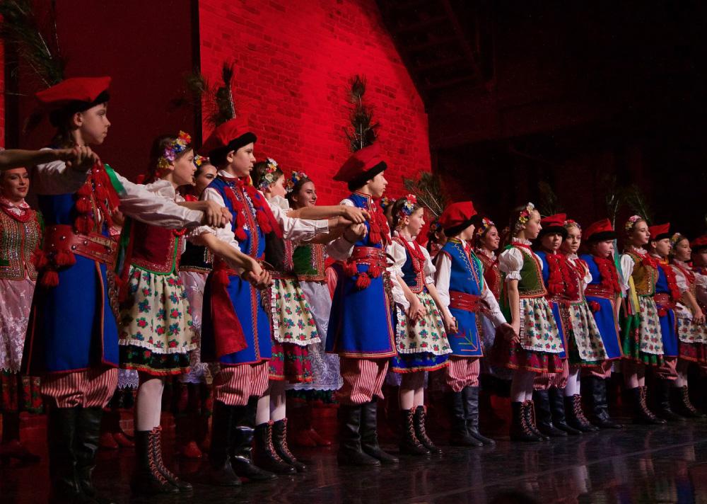 Grupa dzieci w krakowskich strojach ludowych na scenie. Naprzemiennie chłopak i dziewczyna. Trzymają się za ręce, jak do ukłonu.