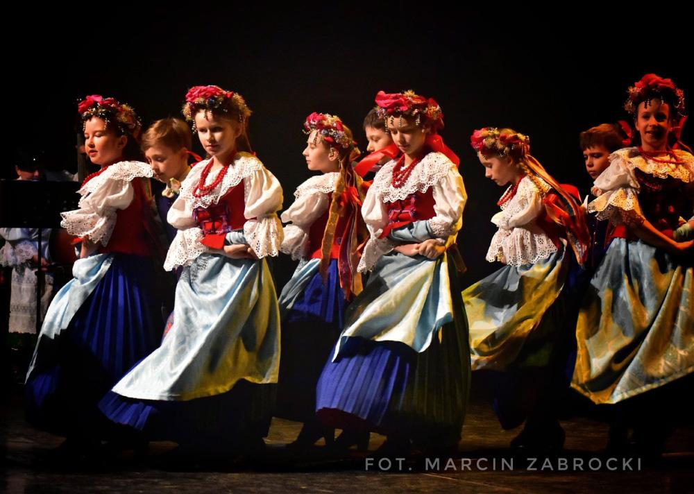 Dziewczynki na scenie w strojach ludowych.