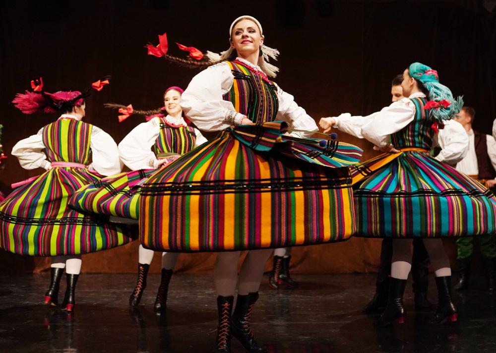 Grupa kobiet w strojach ludowych na scenie. Tańczą, obracają się.