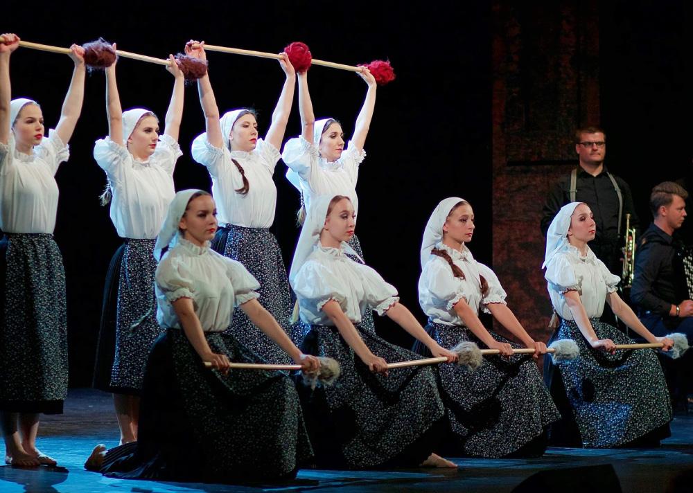 Grupa kobiet na scenie. Cztery z przodu i cztery z tyłu. Ubrane w białe koszule, czarne spódnice, czarno-białe zapaski, na głowie białe chustki. Ręce uniesione nad głowę, a w nich podłużny przyrząd, na jego czubku włóczka.