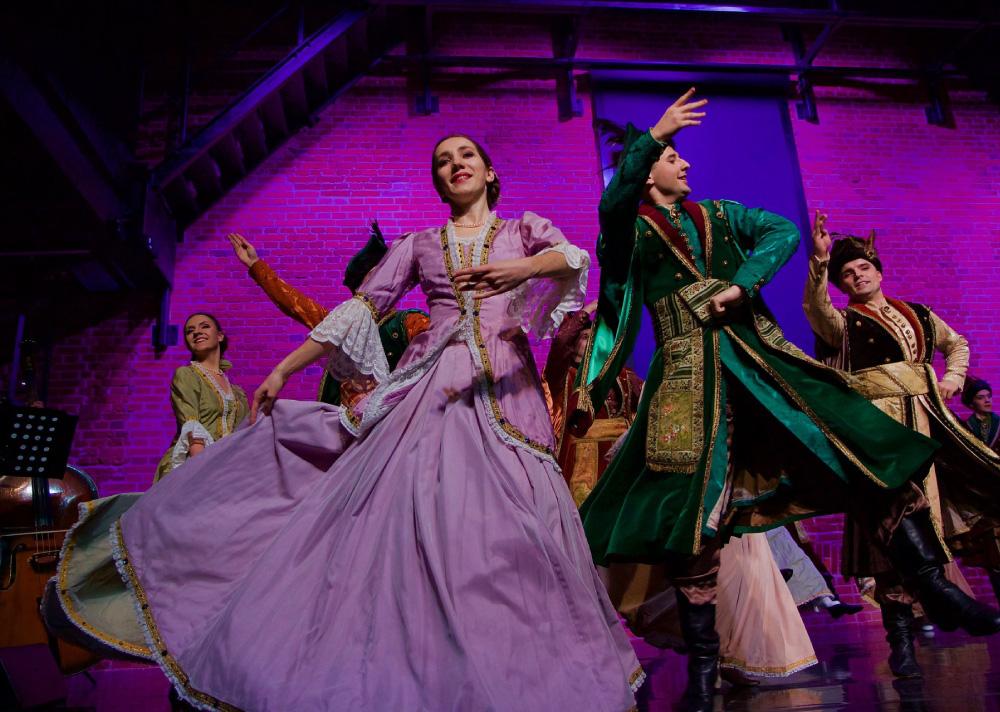 Grupa osób w strojach szlacheckich na scenie. Na pierwszym planie kobieta w fioletowej sukience.