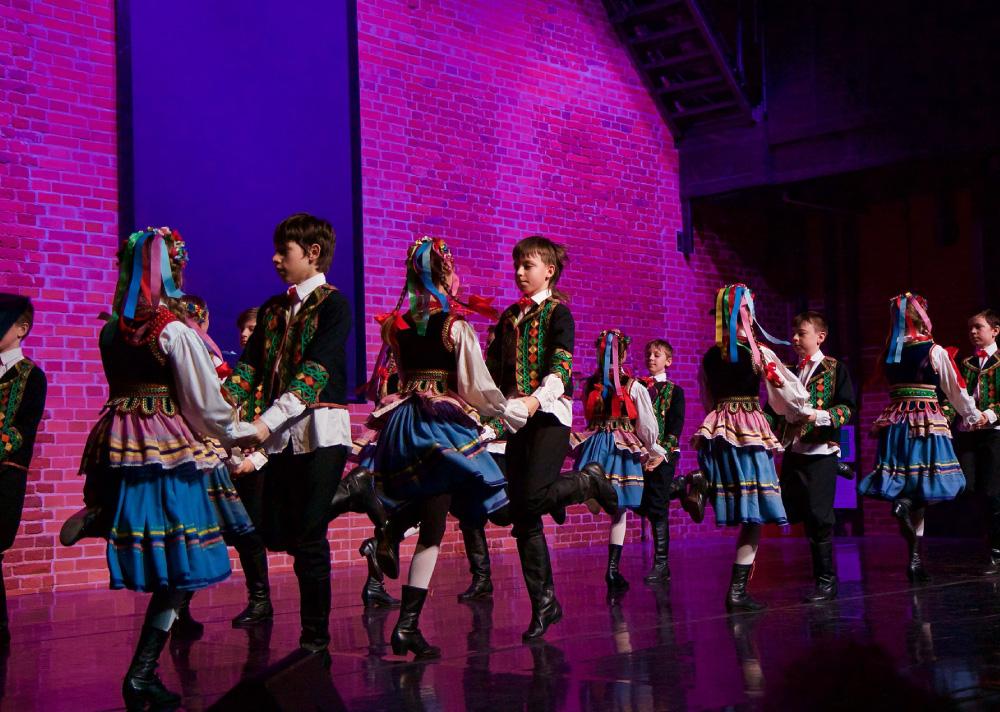 Grupa dzieci w strojach ludowych na scenie. Tańczą w parach ustawionych kolejno obok siebie.