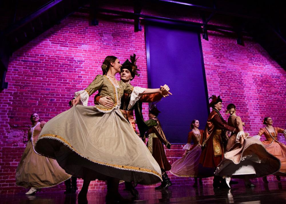 Grupa osób tańczących w parach na scenie w strojach szlacheckich. Na pierwszym planie kobieta w oliwkowej sukience, jedną ręką obejmowana przez mężczyznę.