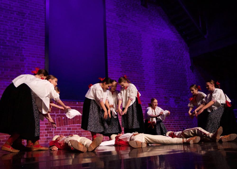 Grupa dzieci w strojach ludowych na scenie. Chłopcy leżą na scenie, dziewczynki pochylają się nad nimi.
