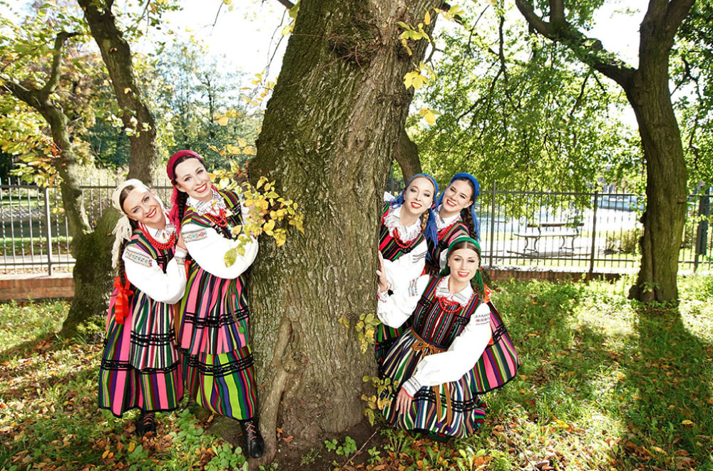 Grupa kobiet w wielokolorowych strojach ludowych wokół drzewa. Dwie z lewej i trzy z prawej. Patrzą w kierunku kamery i uśmiechają się.