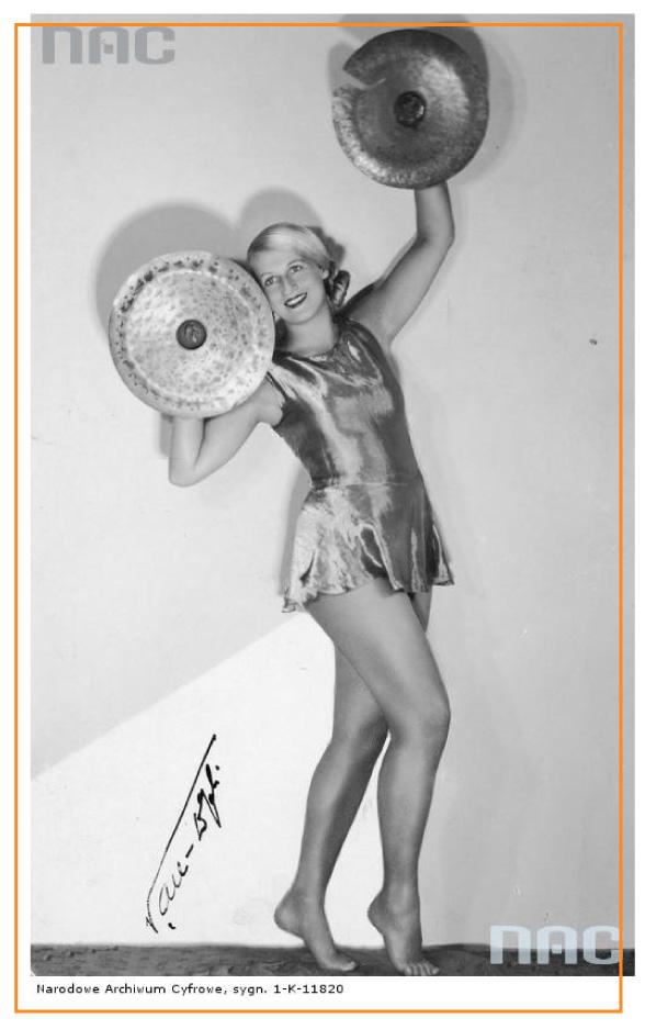 Czarnobiałe zdjęcie. Kobieta w błyszczącym, krótkim stroju. Stoi na palcach. Ręce uniesione, okrągłe przedmioty w dłoniach.