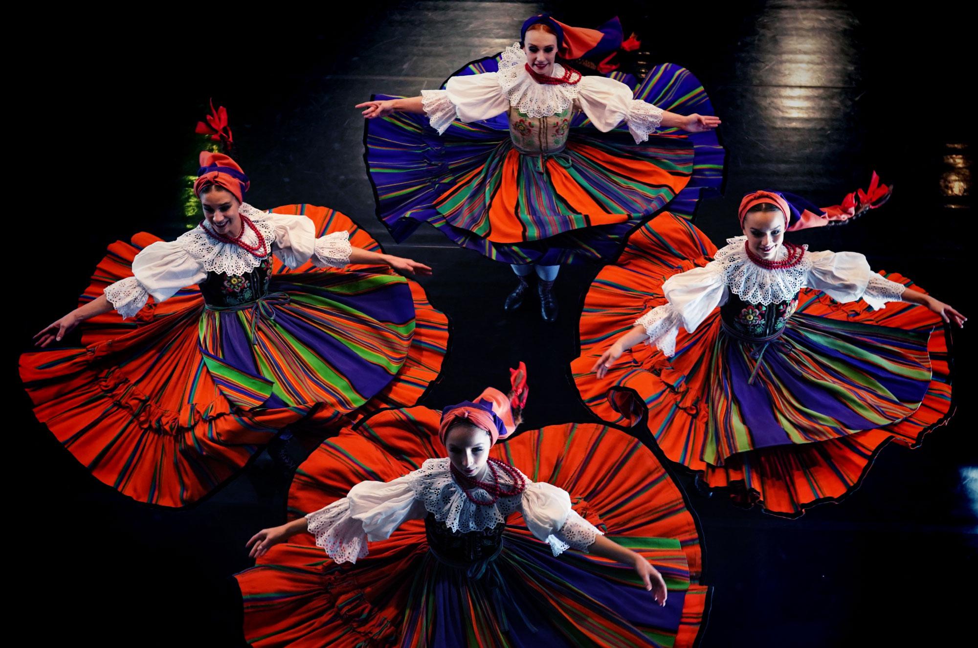 Zdjęcie zrobione z góry. Cztery kobiety w wielobarwnych strojach ludowych w tańcu. Kręcące się spódnice. Ręce otwarte do widowni.