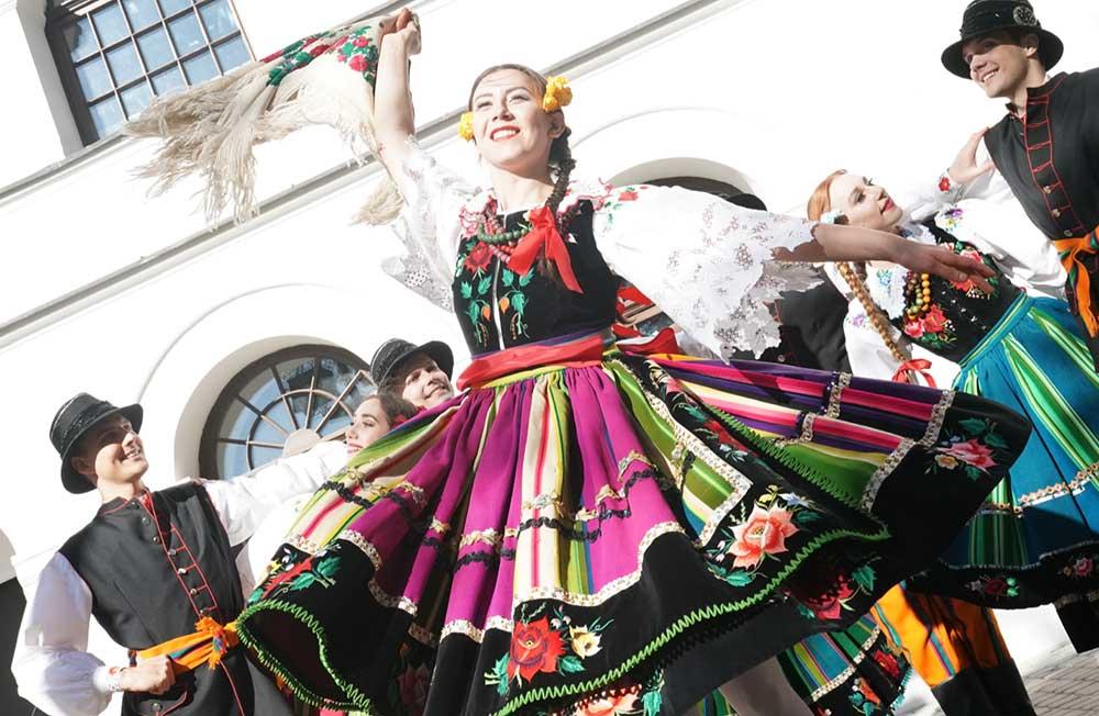 W centrum kobieta, tancerka. Kobieta tańczy, macha chustą. Na sobie ma wielokolorowy strój z regionu łowickiego. W tle inne tańczące pary w strojach łowickich.