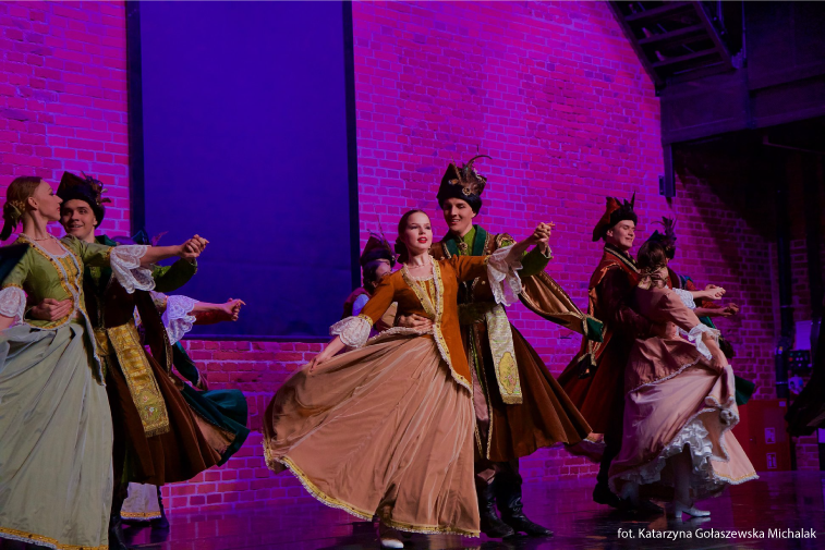 Tanerze tańczący w parach na scenie. Mają na sobie stroje szlacheckie.