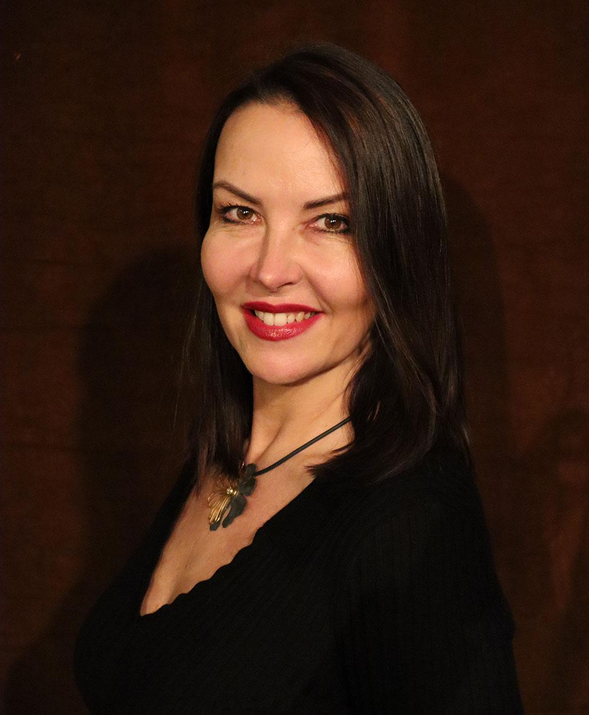 Kobieta ubrana w czarne ubranie, na szyi ma naszyjnik, ciemne włosy do ramion. Przedstawiona od klatki piersiowej w górę. Patrzy w kierunku kamery i uśmiecha się.