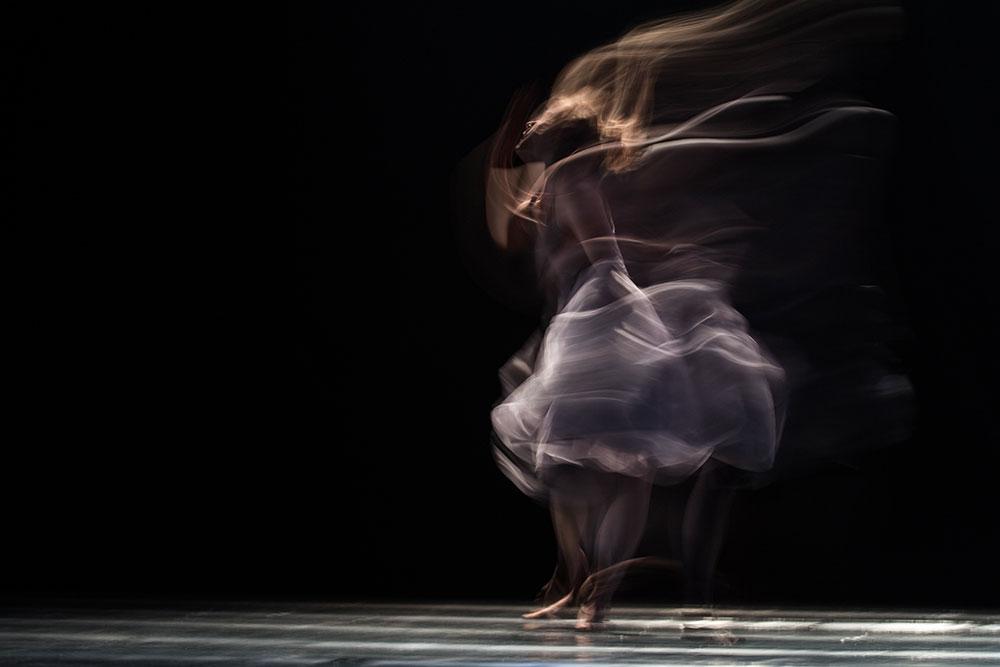 Rozmyta postać kobieca w tańcu na scenie. Ubiera jasną, zwiewną sukienkę. Czarne tło.